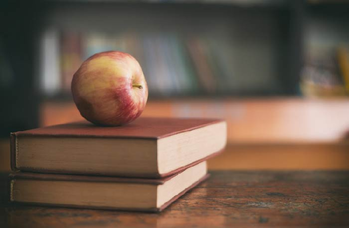 Apple on a desk on top of two books